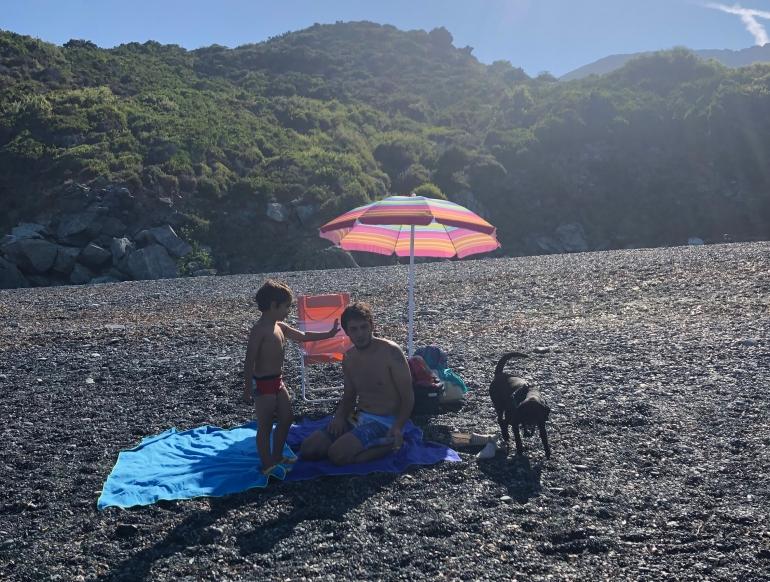 Papà, bambino e cane sulla spiaggia di Nonza, Corsica.